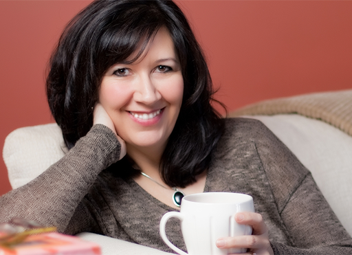 Julianne MacLean sitting with coffee mug in hand, smiling at viewer.
