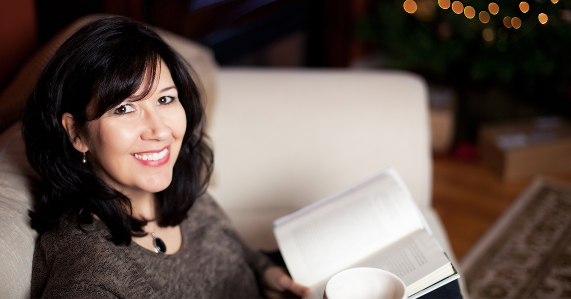 Julianne MacLean sitting with book and coffee in hand, smiling at viewer.