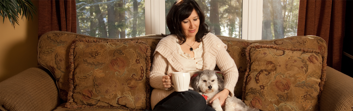 Julianne MacLean sitting with a fluffy grey and white dog, while holding a cup of coffee.